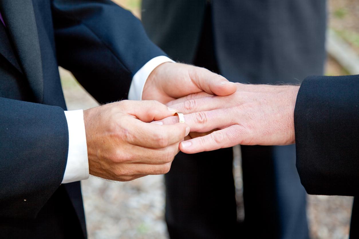 Two men exchange rings at wedding