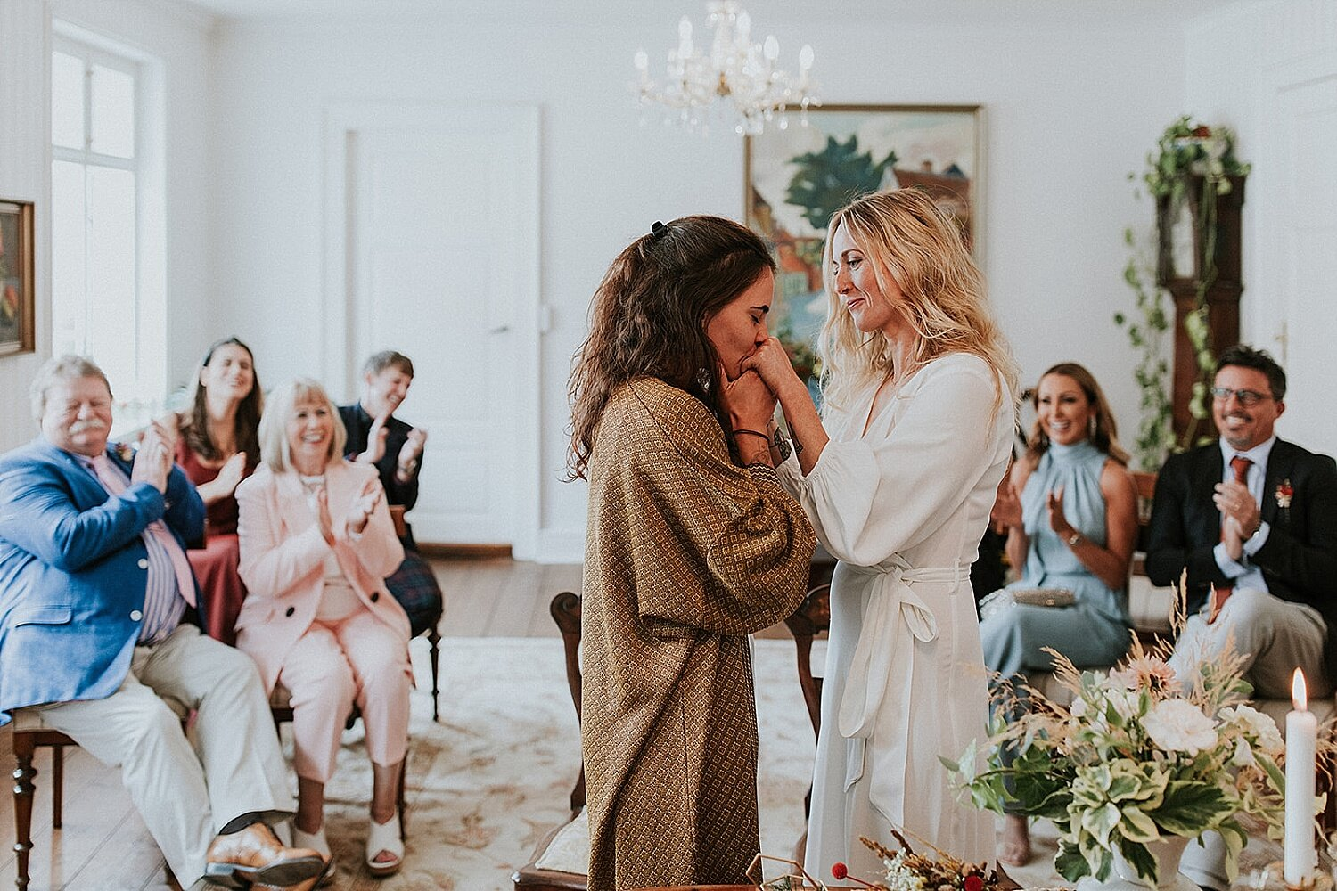 Two brides kissing at wedding ceremony