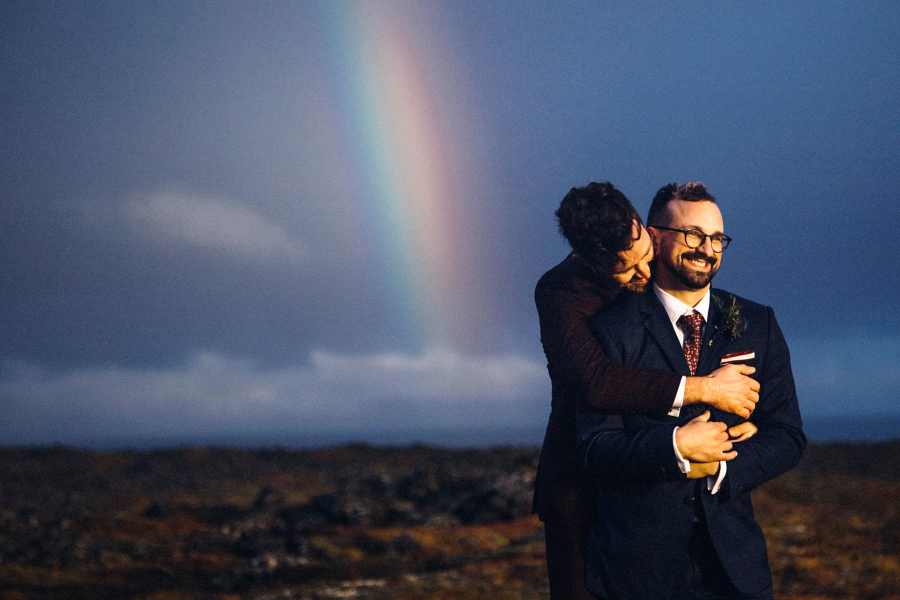 two grooms and rainbow behind them