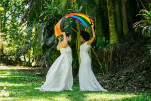 Two brides with rainbow flag